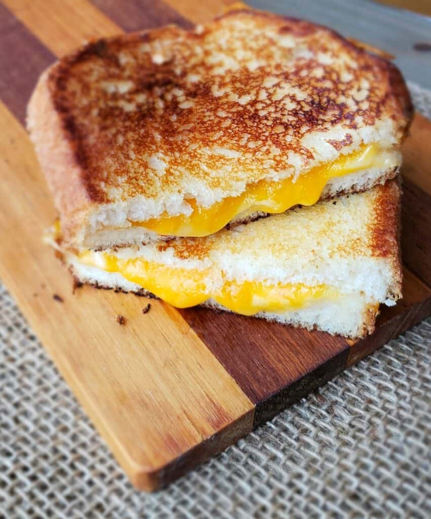 Grilled cheese sandwich cut in half with cheese oozing out