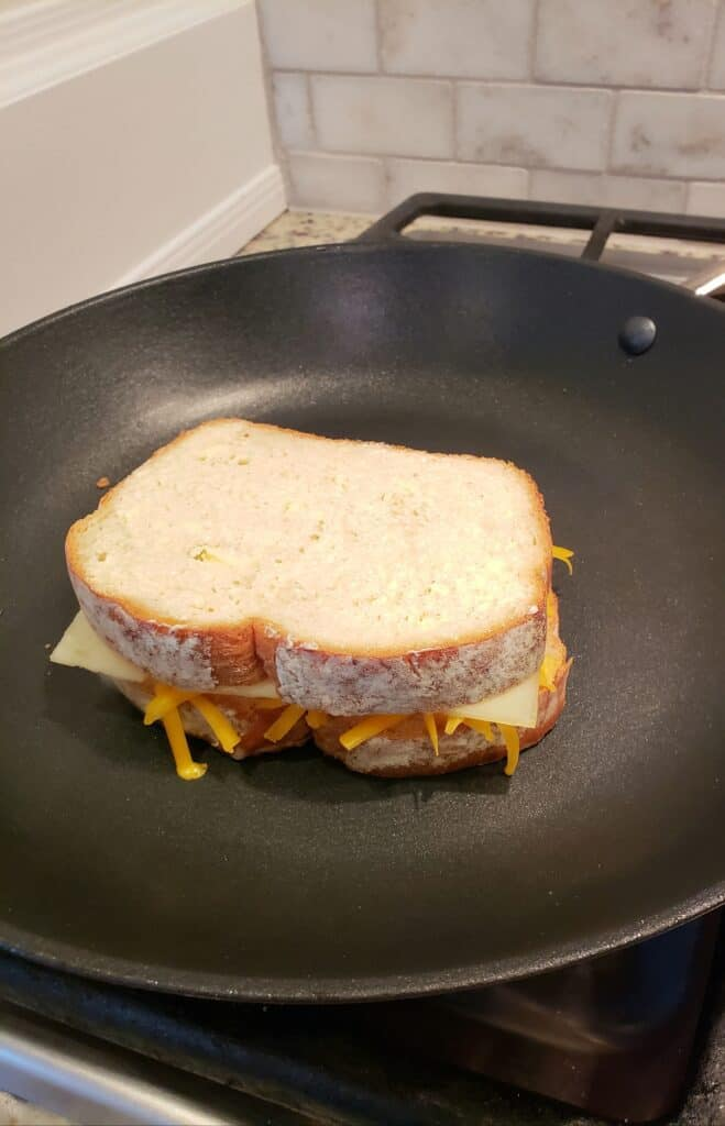 Grilled cheese sandwich in a skillet; top side not grilled yet