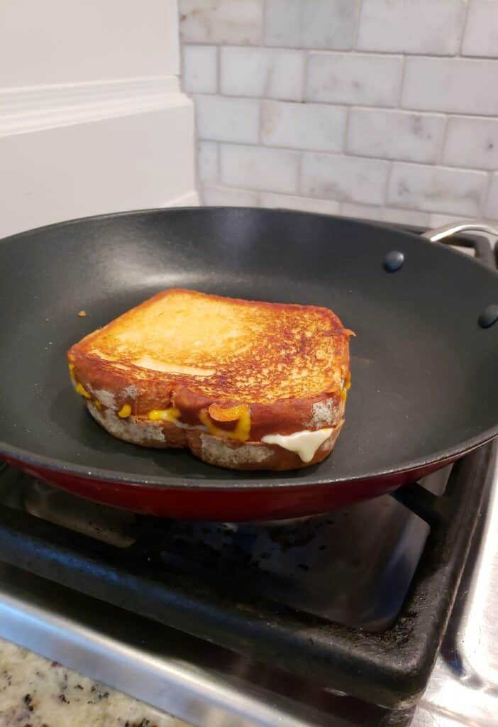 A grilled cheese sandwich in a skillet that has been flipped and grilled side up