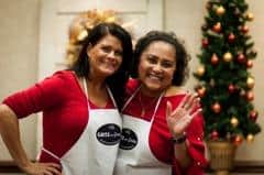 Two ladies in red shirts waving wearing aprons