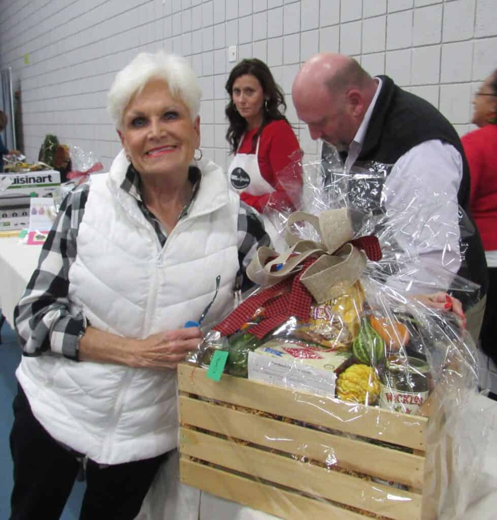 Older attractive lady leaning on wooden gift basket crate