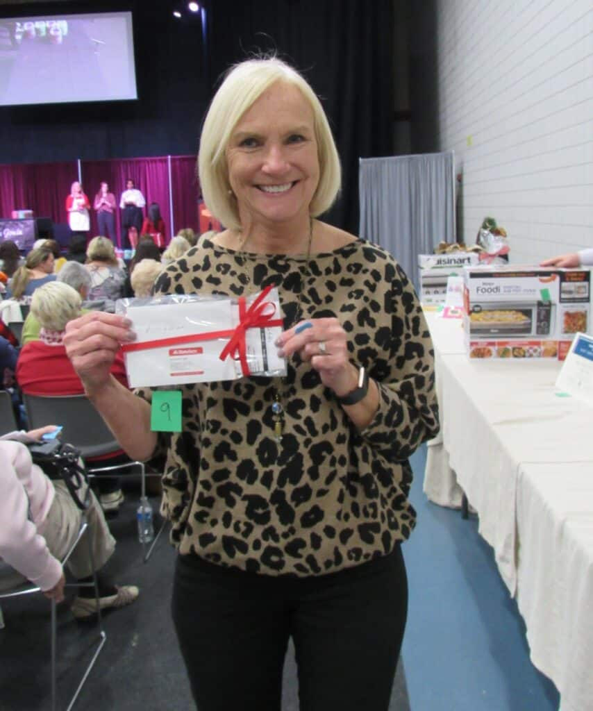 Lady holding a certificate with red ribbon