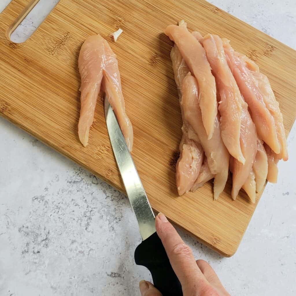 A knife cutting chicken tenders in half on a wooden cutting board.