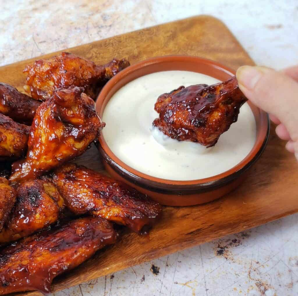 Fingers dipping a bbq chicken drum into Ranch dressing with other wings on the left