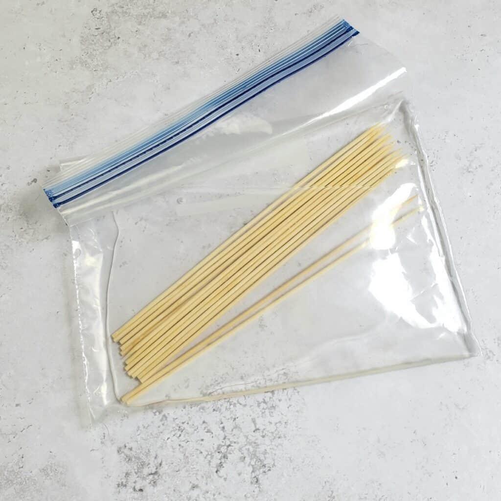 Large zip top plastic bag with wooden skewers soaking in water.