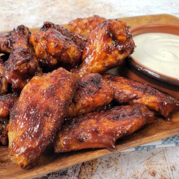 Close up of platter of bbq wings with bowl of Ranch dressing in the background