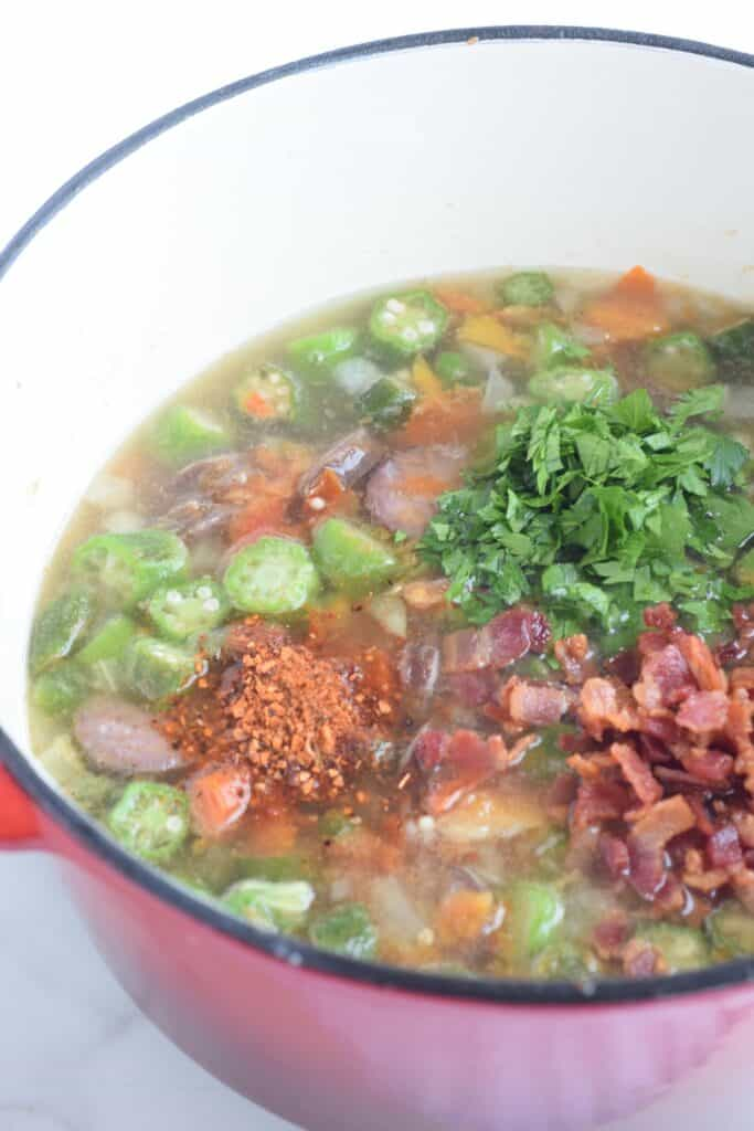 Ingredients for gumbo in white enameled red pot: sausage, okra, tomato, bacon, parsley seasonings