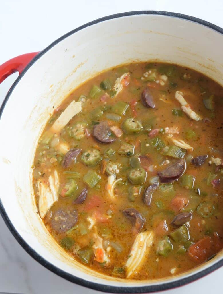 Close up image of chicken sausage gumbo overhead in a white enameled pot