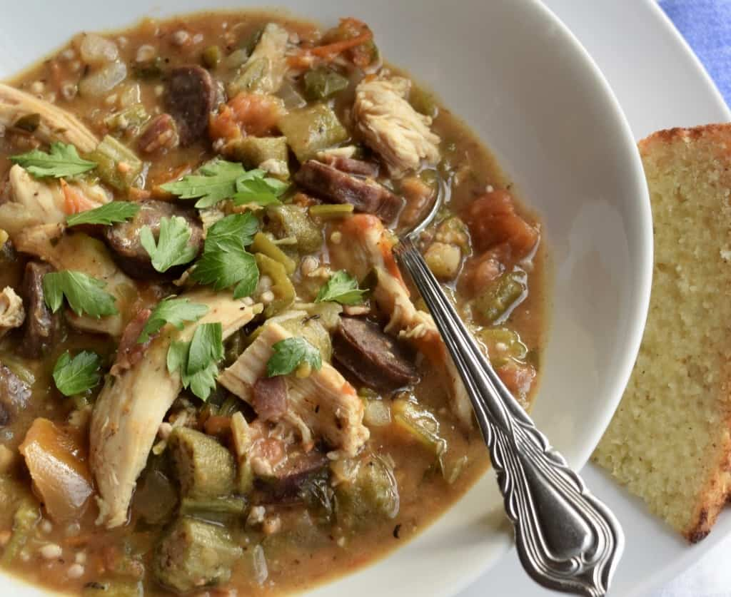 Gumbo in a rimmed bowl with spoon handle in view