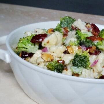 White bowl of broccoli cauliflower salad