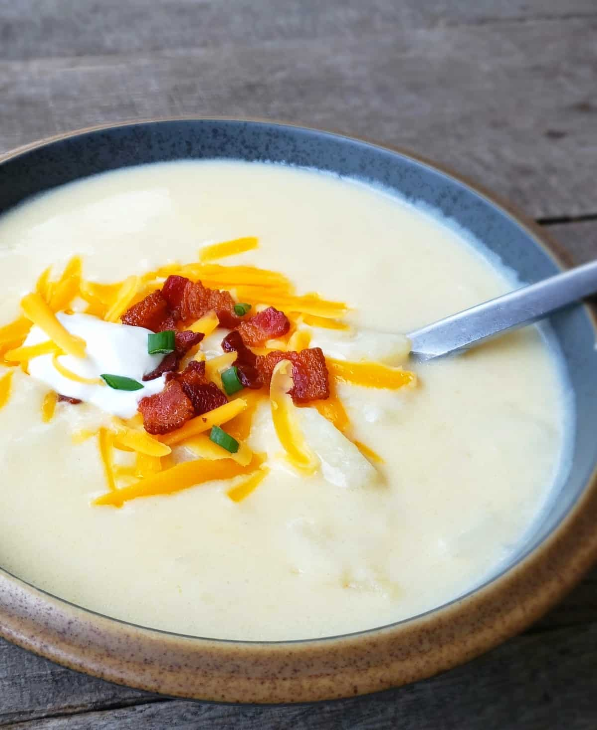 Bowl of loaded potato soup with spoon in it.
