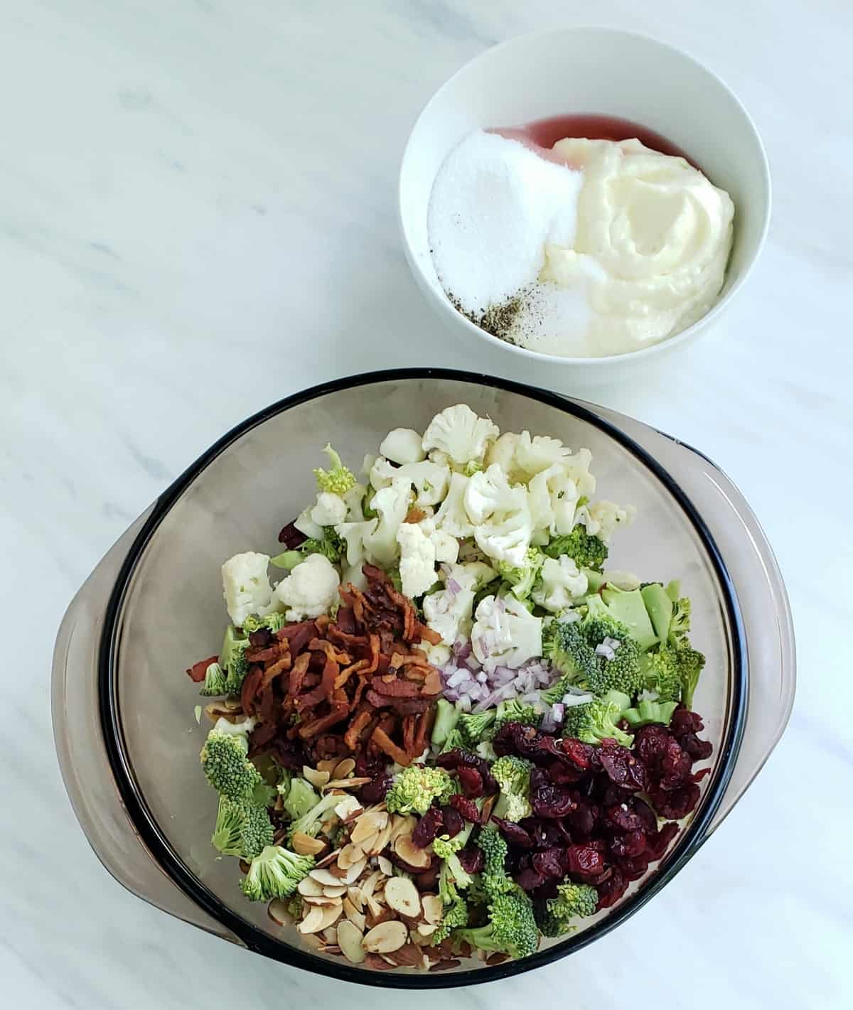 All salad ingredients for this recipe neatly separated in a bowl with dressing ingredients in a smaller bowl