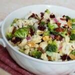 White bowl on pink cloth full of broccoli cauliflower mixture